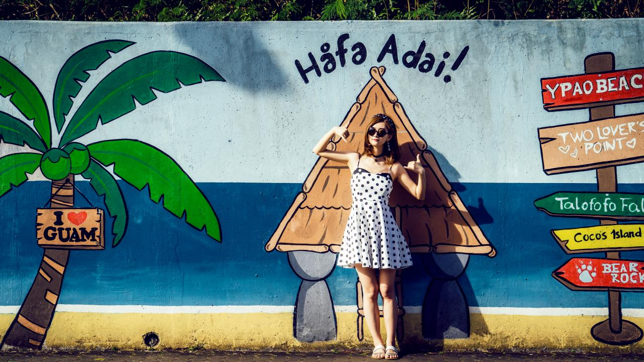 Posing with public mural art in Guam